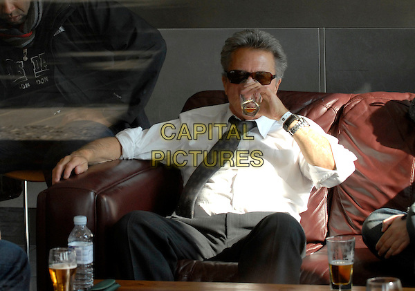 """DUSTIN HOFFMAN .Enjoying a drink at a local bar in between scenes on the set of """"Last Chance Harvey"""" refilming scenes near The Royal Festival Hall, Embankment, London, England..May 21st, 2008.film movie half length sitting beverage sunglasses shades white shirt drinking.CAP/IA.©Ian Allis/Capital Pictures."""
