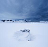 Rock in snow covered field, Vestvågøy, Lofoten islands, Norway