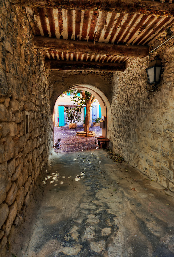 A stone passageway with a wood beam ceiling and an arch, in Ventabren, France