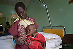 Ajok Uogu feeds her 2-year old daughter Awok a nutritional supplement in the St. Daniel Comboni Catholic Hospital in Wau, South Sudan. Drought and armed conflict have pushed tens of thousands of people in Wau out of their homes, away from their farms, and unable to adequately feed themselves. The child was admitted to the hospital with severe malnutrition.<br /> <br /> Norwegian Church Aid, a member of the ACT Alliance, has provided relief supplies to the displaced in Wau, and has supported the South Sudan Council of Churches as it has struggled to mediate the conflict in Wau.