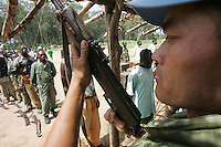 A nepalese UN MONUC peace keaper secures a weapon while Former FLAPC militia gun men wait to hand their weapons to the United Nations in Aru, Ituri region of Eastrern DRC on April the 13th 2005.  a group of more than 200 militias disarm every day in the Aru DDR (Disarmament demobilization reintegration) site under the supervision of the UNDP ( united nations development program). most of these men are belonging to the FLAPC milita group.