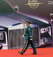 A security guard walks pass an billboard of Guanzhou Luxury Goods Fair in China.