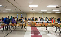 NWA Democrat-Gazette/BEN GOFF @NWABENGOFF<br /> People line up to receive meals Thursday, Nov. 28, 2019, during the annual Thanksgiving meal distribution at the First Baptist Church Olive Street campus in Rogers. <br /> <br /> Paul Olinger, a church member who helped coordinate the meal, said the event started 20 years ago 'As an outreach of the church to show the love of Christ in the community'. Volunteers from the church and the community cooked, packaged and delivered boxed meals that included ham, green beans, mashed potatoes and deserts. <br /> <br /> Open to anyone, a line wrapped around the room as families picked up boxes of food to take home, but Olinger estimates that 98 percent of the meals are delivered by volunteers.