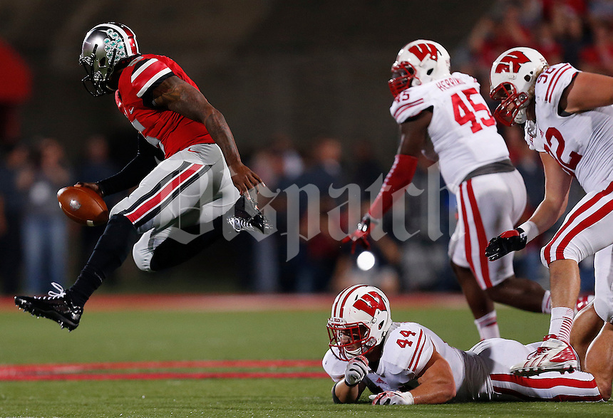 Ohio State Buckeyes quarterback Braxton Miller (5) dodges a tackle from Wisconsin Badgers linebacker Chris Borland (44) in the second quarter of the NCAA football game at Ohio Stadium in Columbus, Saturday evening, September 28, 2013. As of halftime the Ohio State Buckeyes led the Wisconsin Badgers 24 - 14. (Columbus Dispatch  / Eamon Queeney)