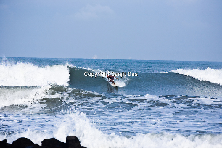 "Kirtan Ananda, one of the Krishna devotees from the Kaliya Mardana Krishna Ashram is seen surfing on the Arabian Sea on the beach front of Mangalore, Karnataka, India.  ..Krishna devotees in the Gaudiya Vaishnava tradition of Hinduism, they are known collectively as the ""surfing swamis."" The ""surfing ashram"" is growing in popularity and surfing here is a form of meditation, a spiritual practice leading to heightened states of awareness."