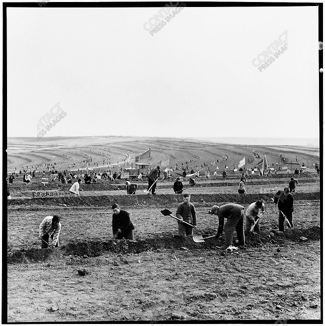"""Educated youth"" and local peasants of the Xingan production brigade work on an arid field's terrace irrigation system. Xinsheng commune, Baiquan county, 10 November 1975"