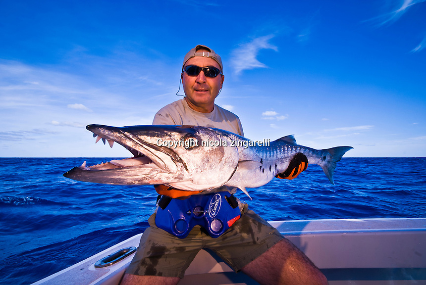 October 2008, Bermuda. An happy fisherman in his 50s holding a Barracuda (Sphyraena barracuda) caught with an artificial lure in the waters of Bermuda, Atlantic Ocean. Horizontal