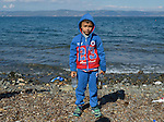 A refugee child stands on a beach near Molyvos, on the Greek island of Lesbos, on October 29, 2015, after he and his family crossed the Aegean Sea from Turkey in a small overcrowded boat provided by Turkish traffickers to whom the refugees paid huge sums. They were received in Greece by local and international volunteers, then proceeded on their way toward western Europe.