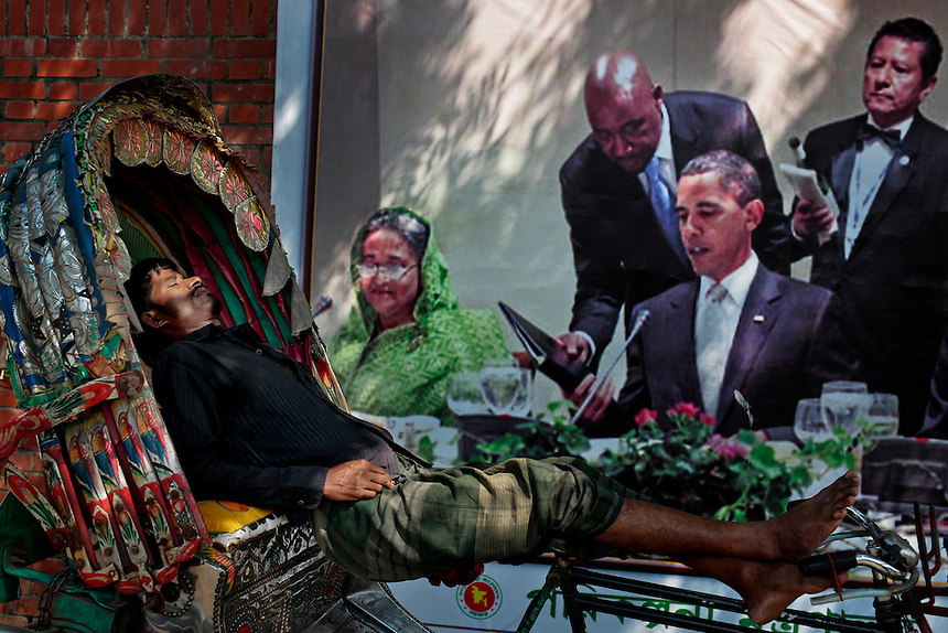 A Bangladeshi rickshaw puller takes a nap on his rickshaw next to a banner printed portraits of American President Barack Obama, right, and Bangladesh's Prime Minister Sheikh Hasina, left, on a road in Dhaka, Bangladesh.