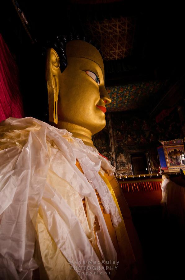 Gilded copper Buddha inside the central shrine at Naropa Royal Palace, Shey, Ladakh, India.