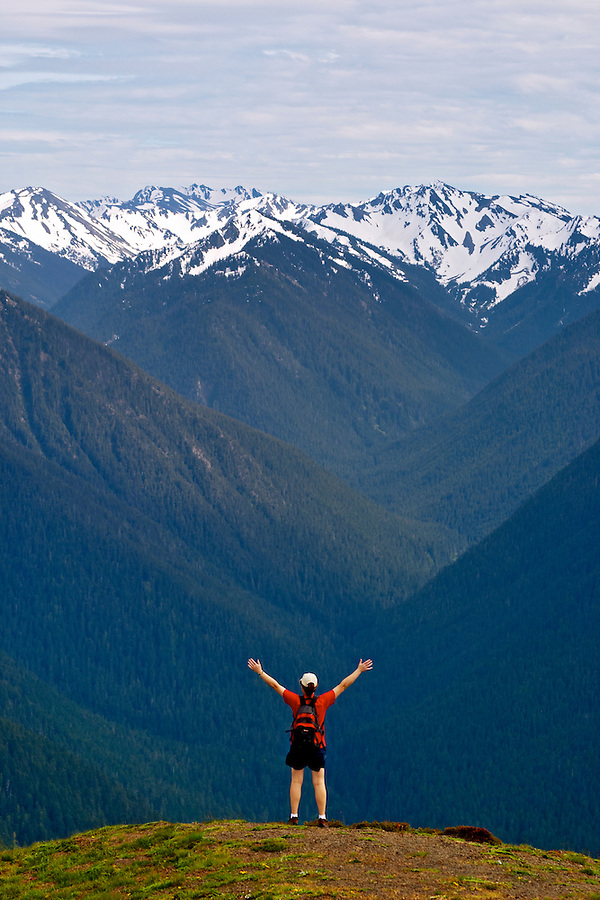 Woman standing with arms streatched above head in front of Olympic Mountains, Hurricane Ridge, Olympic National Park, Olympic Peninsula, Clallam County, Washington, USA