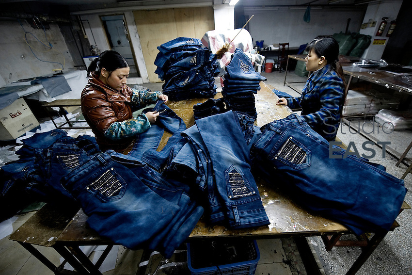 Workers sew blue jeans in a little workshop by the street in Xintang, Guangdong province, China, on February 10, 2012. Photo by Lucas Schifres/Pictobank