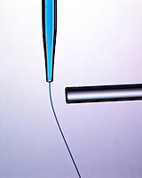 STREAM OF POLAR LIQUID DEFLECTED BY CHARGED ROD (2 of 2)<br /> Water Is a Polar Liquid<br /> A stream of blue-dyed water is deflected because its molecules are attracted toward the charge.