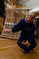Reimei Yokoyama stringing a bow. Yokoyama Reimei Bowmakers, Miyakonojo, Miyazaki Prefecture, Japan, December 23, 2016. A handful of bowyers from the Kyushu city of Miyakonojo make over 90% of all the bows used in traditional Japanese archery. The bows are made from laminated bamboo and haze wood in process that consists of over 200 individual tasks. At over two meters from tip to tip the bows the longest used in the world.