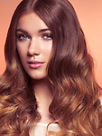 Beauty portrait of a young woman with long wavy brown hair