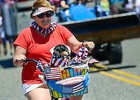 A woman rides a bicycle while carrying a dog in the front basket with independence theme during the Independence Parade Saturday July 2, 2016 on Beach Avenue in Cape May, New Jersey. Photo by William Thomas Cain/Cain Images