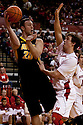 29 February 2012: Andrew Brommer #20 of the Iowa Hawkeyes passes the ball under the hoop against Mike Fox #33 of the Nebraska Cornhuskers at the Devaney Sports Center in Lincoln, Nebraska. Iowa defeated Nebraska 62 to 53.