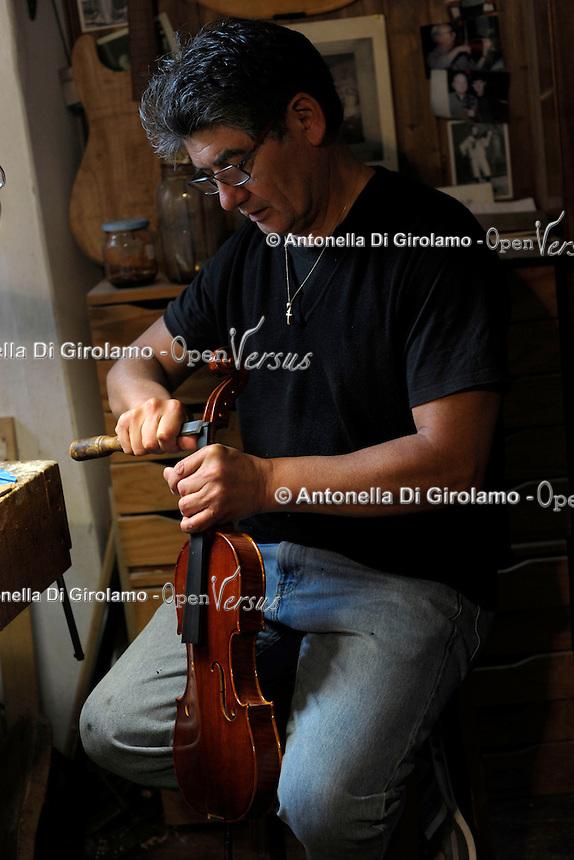 """Il maestro Carlos Roberts, liutaio del Consorzio Liutai """"Antonio Stradivari"""", mentre costruisce un  violino, nel suo laboratorio. .The master Carlos Roberts while building a violin in his laboratory.The Consortium of Violinmakers.."""