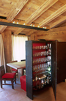 An iron cabinet made by the local blacksmith Fabbro Candeago for storing glasses also serves as a freestanding wall between the dining area and the entrance to the chalet
