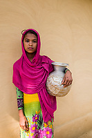 Bangladesh, Teknaf, Cox's Bazar. Leda Rohingya Refugee Camp. The Rohingya, a Muslim ethnic group  denied citizenship in Burma/Myanmar have escaped persecution from Burmese militants in their country. There are up to 500,000 refugees and migrants living in makeshift camps in Teknaf, Cox's Bazar. <br /> Young girl collecting water at the well.