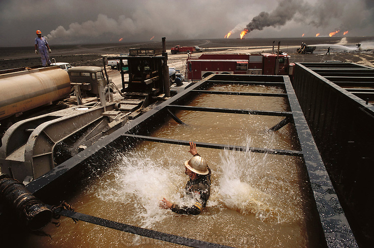 A firefighting oil well worker employed by Safety Boss of Canada cools off in a tank of seawater in July 1991 during efforts to cap a well during the Kuwait Oil Well Fires. Ambient temperatures in the July desert exceeded 120 degrees F and often went much higher. More than 700 wells were set ablaze by retreating Iraqi troops creating the largest man-made environmental disaster in history.