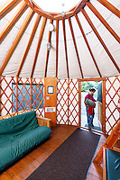 Woman carrying camping gear through doorway of rental yurt at Kayak Point County Park, Snohomish County, Washington, USA
