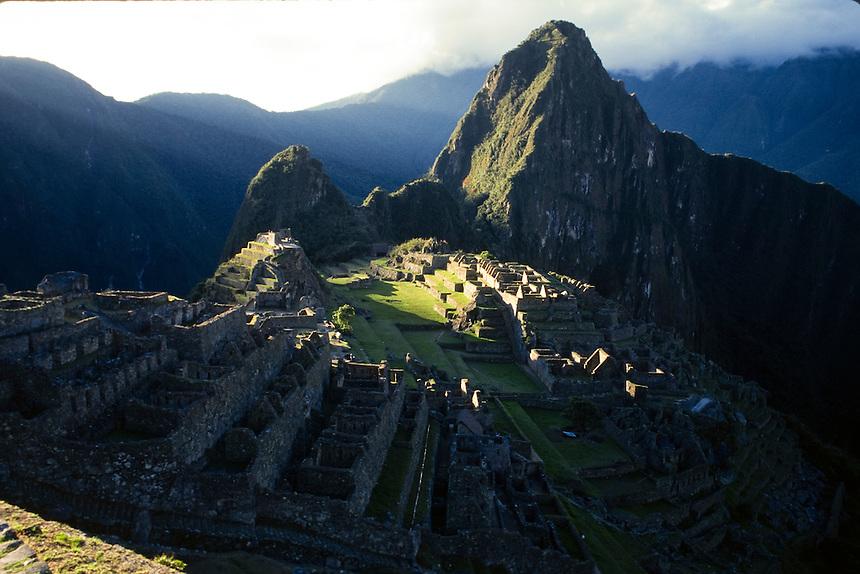 Patches of sunlight break through the clouds over the Inca citadel of Machu Picchu in central Peru.