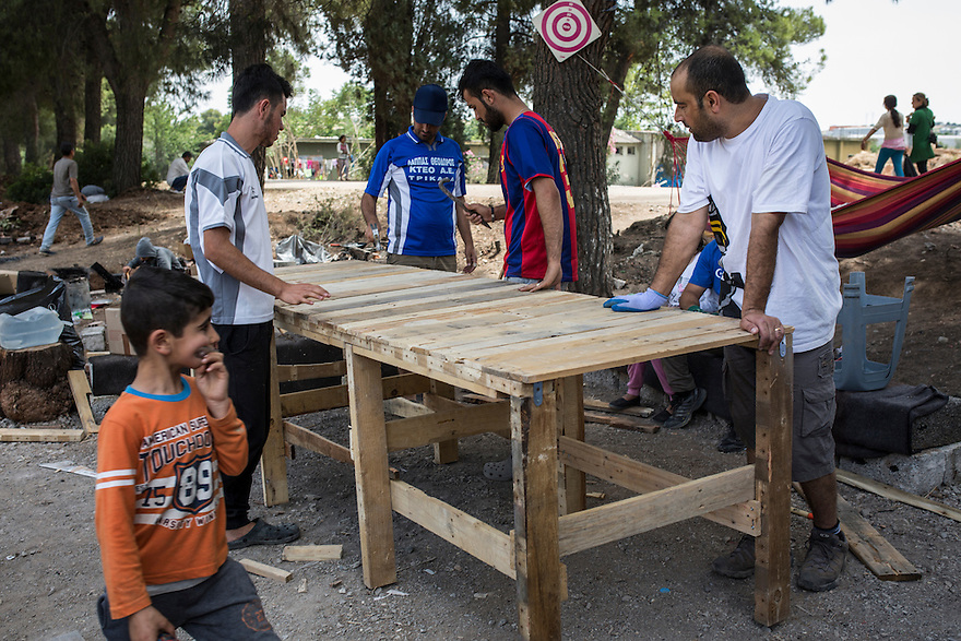 Noh family members construct a large table out of pallets and tools donated to them by volunteers at Ritsona Camp. The family are Yazidi and immigrated from Iraq due to the ISIS threat nearby. PHOTO BY JODI HILTON/PULITZER CENTER