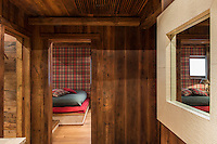 A glimpse from a wood-clad corridor into one of the guest bedrooms which is decorated in cheerful plaid