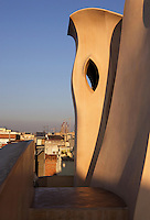 Chimney with La Sagrada Familia in the distance, Roof, La Pedrera (Casa Milà), Barcelona, Catalonia, Spain, built by Antoni Gaudí (Reus 1852 ? Barcelona 1926), 1906 - 1910, for  Milà Family, with Joan Beltran as a plaster and with Josep Maria Jujol as architect collaborator. One of the main Gaudi residential buildings. Picture by Manuel Cohen