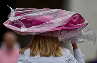 LOUISVILLE, KY - MAY 05: A woman uses a poncho to protect her hat from the rainstorm on Kentucky Oaks Day at Churchill Downs on May 5, 2017 in Louisville, Kentucky. (Photo by Jesse Caris/Eclipse Sportswire/Getty Images)