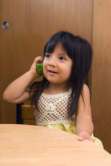 Berkeley CA Girl, age two and a half, Guatemalan, engaged in lively fantasy conversation using toy cell phone  MR