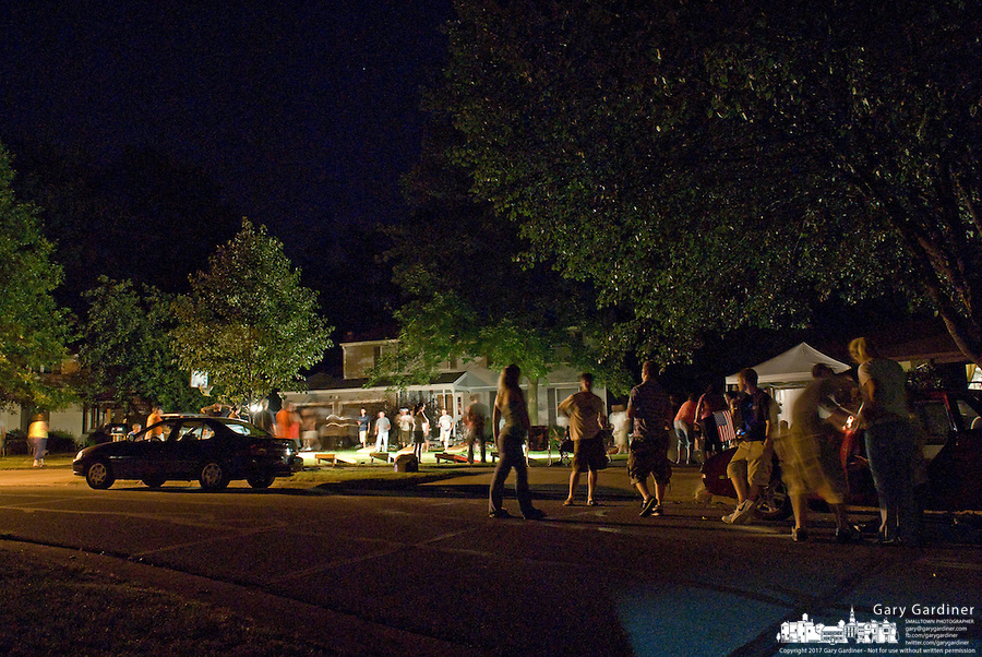 Crowd gathers in street at cornhole tournament in a neighborhood