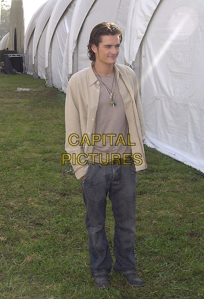 ORLANDO BLOOM.December 2003.full length necklaces beige shirt jeans denim hands in pockets.www.capitalpictures.com.sales@capitalpictures.com.© Capital Pictures.