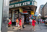 New York, NY 7 July 2014 - Girls in red dresses pass a Canal Street souvenir shop © Stacy Walsh Rosenstock/Alamy