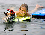 Kieran Mooney, 15, of Tolland, Conn.,  smiles as he sees his dog Pogo start to paddle from the boogie board he's on as they approach shore, Monday, July 7, 2014, on Bolton Lake in Bolton. (AP Photo / Journal Inquirer, Jim Michaud)