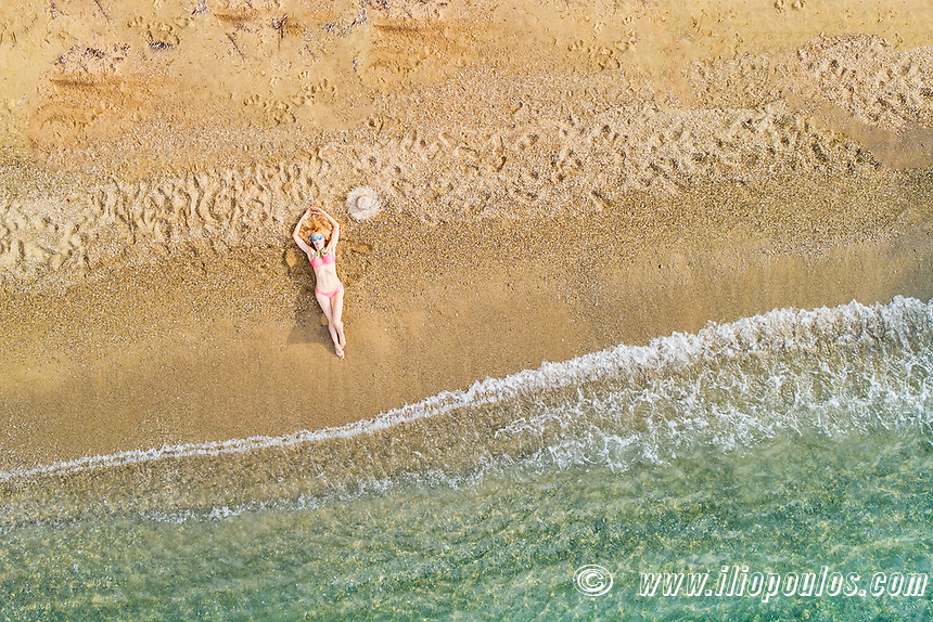 A beautiful woman at the beach Agia Eleni of Skiathos from drone view, Greece