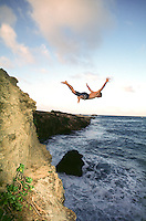 Young man cliff diving of Laie point at sunset.