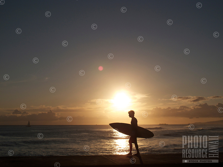 blacklit surfer with board heading out at Waikiki