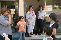 Annie Paule Derczansky (in doorway, L) and Alice Midal (in doorway, R) talk to children and parents visiting an Oriental pastry workshop held by the non-profit association Batisseusses de Paix (or Women Peace Builders) that seeks to build ties between Muslim and Jewish women, in a restaurant in Creteil, outside Paris, France, 24 June 2008.