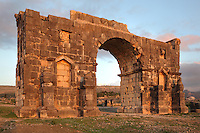 Rear of the Triumphal Arch of Caracalla, built 217 AD by the city's governor Marcus Aurelius Sebastenus at the end of the Decumanus Maximus in honour of Emperor Caracalla, 188-217 AD, and his mother Julia Domna, Volubilis, Northern Morocco. The arch was reconstructed 1930-34 and was originally topped with a bronze chariot pulled by 6 horses. Volubilis was founded in the 3rd century BC by the Phoenicians and was a Roman settlement from the 1st century AD. Volubilis was a thriving Roman olive growing town until 280 AD and was settled until the 11th century. The buildings were largely destroyed by an earthquake in the 18th century and have since been excavated and partly restored. Volubilis was listed as a UNESCO World Heritage Site in 1997. Picture by Manuel Cohen