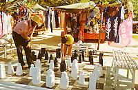 Father and son playing game of chess outdoors with giant pieces in hotel gardens. Malaysia..