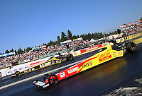 Aug. 3, 2014; Kent, WA, USA; NHRA top fuel dragster driver Antron Brown (near) races alongside Tony Schumacher during the Northwest Nationals at Pacific Raceways. Mandatory Credit: Mark J. Rebilas-USA TODAY Sports