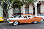 Havana, Cuba; a classic orange and white 1957 Ford Fairlane driving along the Paseo de Marti past the Saratoga Hotel