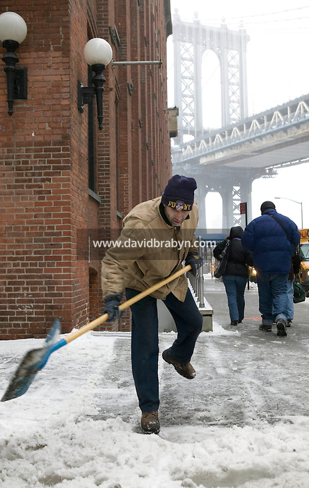 14 February 2007 - New York City, NY - A man clears snow off the sidewalk in Brooklyn, New York City, USA, as the first snow storm of the year hits the city, 14 February 2007. The Manhattan Bridge is seen in the background.