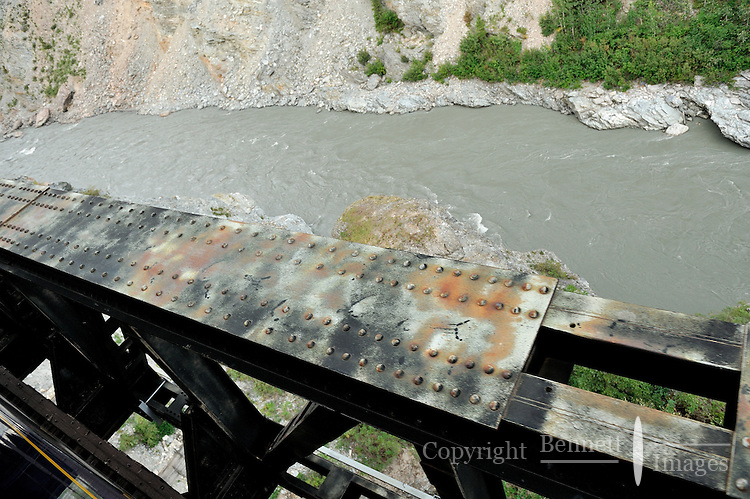 A bridge with a distinctive pattern of rivets overlooks the Nenana River Canyon. The Alaska Railroad's Denali Star train runs between Anchorage and Fairbanks, with Denali one of the stops along the way.