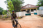 Sri Lankan Government health centre is seen against the Sri Lankan army soldier patrolling in Punaineeravi village in Kilinochchi in Northern Sri Lanka. Photo: Sanjit Das/Panos