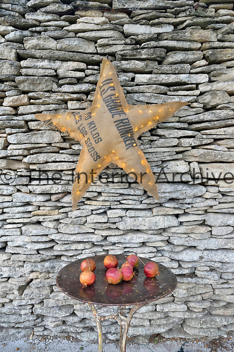 A small table of pomegranates is placed beneath an illuminated star against a dry stone wall of the terrace