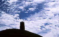Glastonbury Tor and the remains of the chapel of St Michael de Torre seen in silhouette, Somerset, England, UK May 1996
