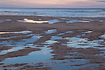 Evening beach scene with reflections of sky in sand puddles
